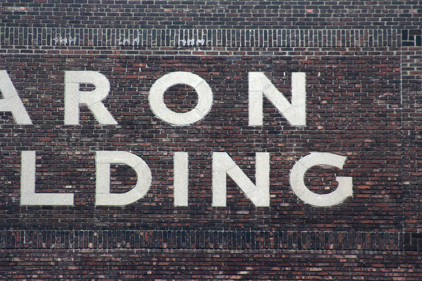 Inlaid limestone lettering on the side of the Caron Building