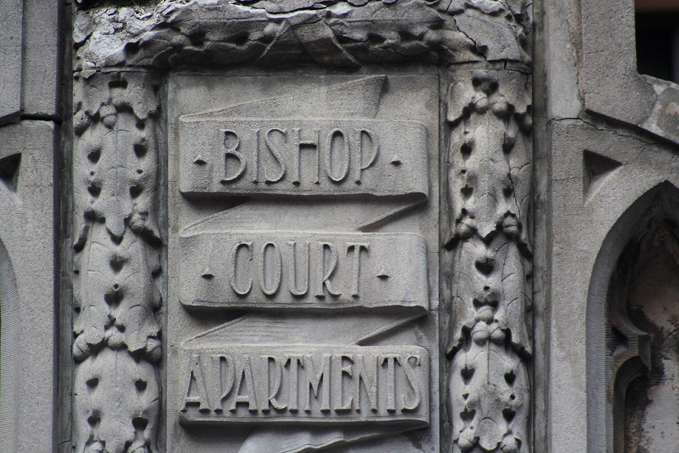 Raised sandstone inscription on the Bishop Court Apartments facade at the corner of rue Bishop and boulevard de Maisonneuve Ouest.